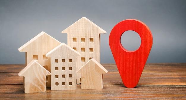 Casas de madera en miniatura y un marcador de geolocalización. ubicación de edificios residenciales.