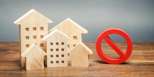 Casas de madera y una señal de prohibición. vivienda inaccesible y cara. restricciones