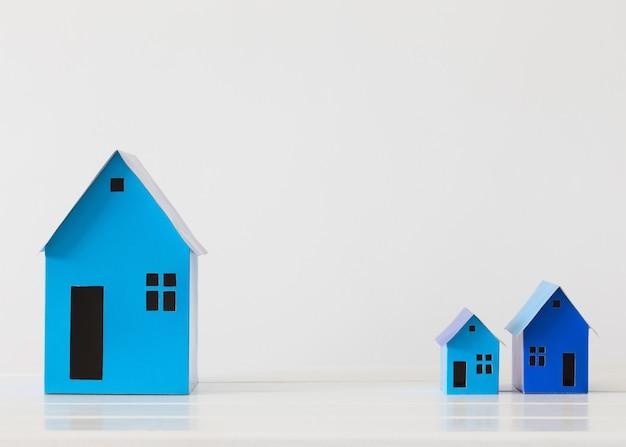Casas de papel azul en espacio en blanco