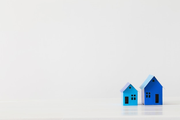 Casas de papel azul sobre fondo blanco.