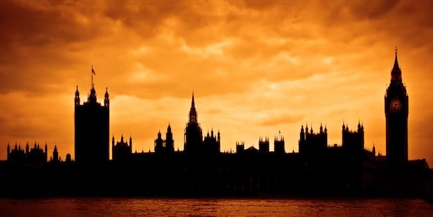 Casas del parlamento al atardecer, silueta sobre cielo dramático