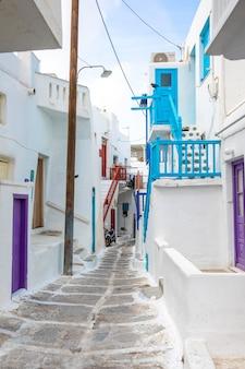 Casas tradicionales con puertas y ventanas azules en las estrechas calles de la aldea griega en mykonos, grecia
