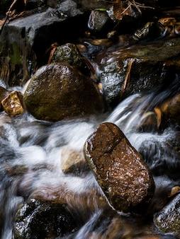 Cascada de la cala de la corriente de la montaña que atraviesa rocas en un bosque tropical.