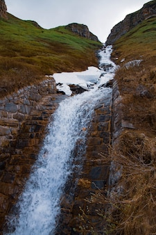Cascada cayendo sobre rocas cubiertas de musgo