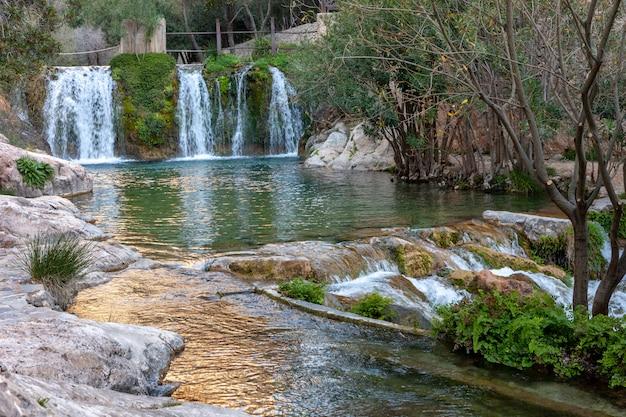 Cascada con estanque de agua verde.