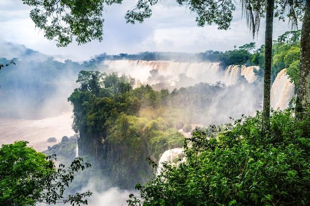 Cascada en el parque nacional iguazú rodeado de bosques cubiertos de niebla bajo un cielo nublado