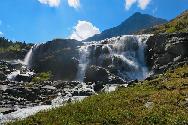 Cascada que fluye en día soleado. montañas de altai, siberia, rusia