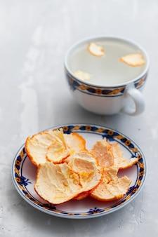 Cáscara de naranja en un plato y en una taza con agua caliente