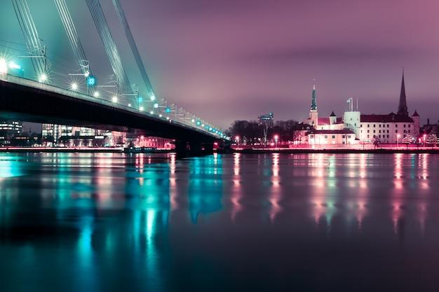 Casco antiguo y el río daugava en la noche, riga, letonia