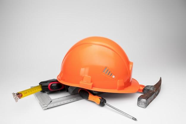 Casco de construcción blanco, cinta métrica, martillo, destornillador. concepto de arquitectura, construcción, ingeniería, diseño, reparación. copia espacio