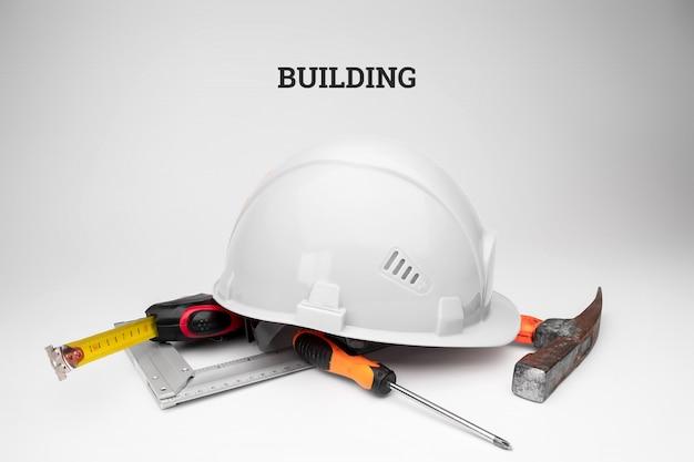 Casco de construcción blanco, cinta métrica, martillo, destornillador. construcción de la inscripción. concepto de arquitectura, construcción, ingeniería, diseño, reparación.