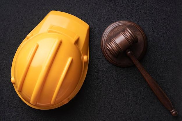 Casco de construcción y mazo de jueces sobre fondo negro. vista superior. construcción y derecho.