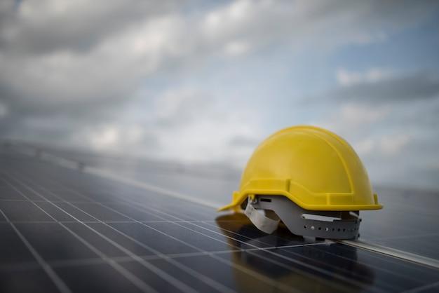 Casco de seguridad amarillo en el panel de la célula solar