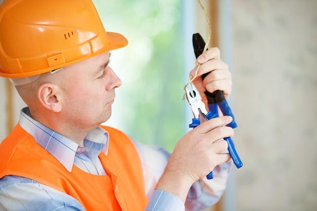 Un casco de electricista reparando el cableado del techo en la casa