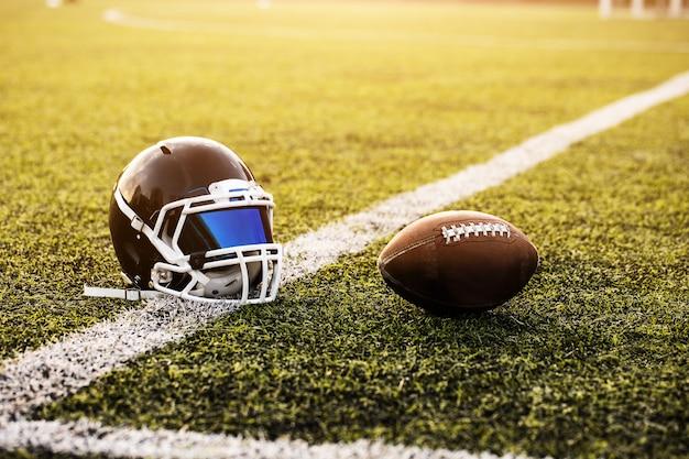 Casco de fútbol americano y pelota sobre hierba verde