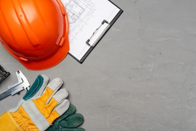 Casco, guantes y planos de una vista superior de constructor