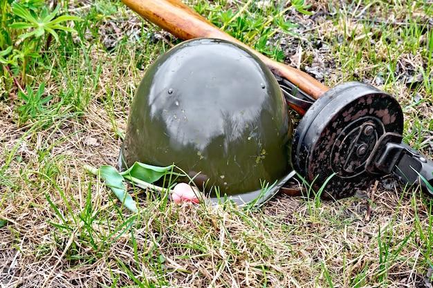 Un casco y una metralleta de los tiempos de la gran guerra patria, una bolsa de color protector y un tulipán contra el fondo de hierba