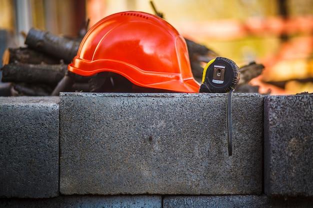 El casco naranja de construcción y la ruleta de construcción están en el bloque de cemento
