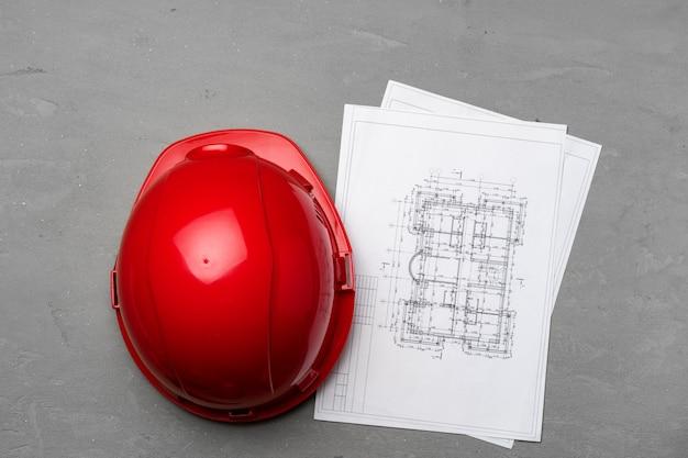 Casco y planos de arquitecto sobre superficie de madera