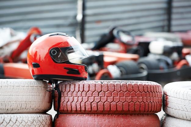 Casco rojo con visera sobre neumáticos