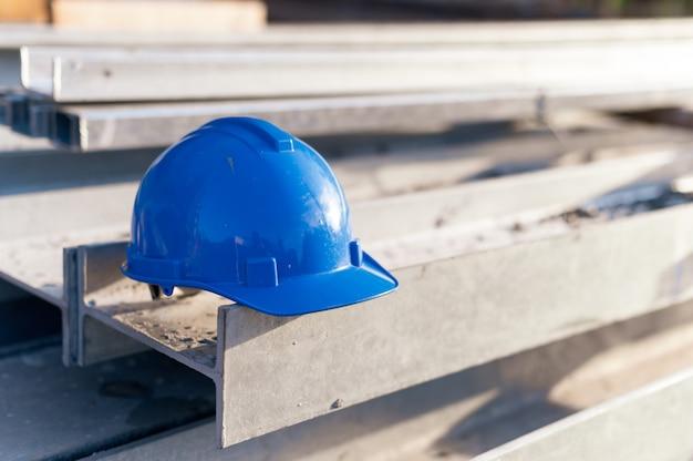 Casco de seguridad azul colocado en estructura de acero en el sitio de construcción