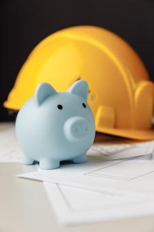 Casco de seguridad de construcción y concepto de inversión y construcción de hucha azul