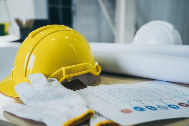 Casco de seguridad y guantes en la mesa en el sitio del proyecto