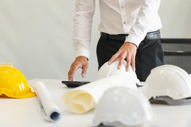 Casco de seguridad en la mesa en la oficina, concepto de ingeniero trabajo en equipo de construcción de edificios