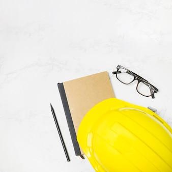 Casco y gafas cerca del diario de construcción