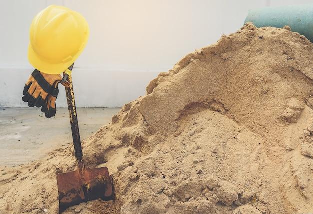 Cascos amarillos, guantes y pala sobre la pila de arena.