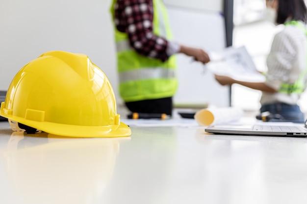 Cascos de seguridad amarillos de ingenieros de primer plano colocados en una sala de reuniones de ingenieros y arquitectos, donde tienen una reunión de planificación de la construcción y una revisión. conceptos de construcción e interiorismo.