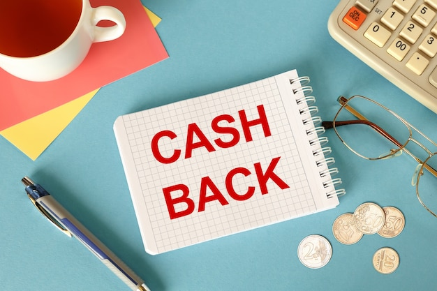 Cash back está escrito en un bloc de notas en un escritorio de oficina con accesorios de oficina.