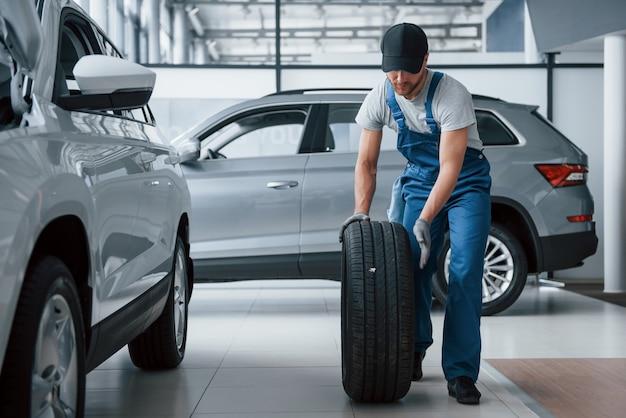 Casi termino. mecánico sosteniendo un neumático en el taller de reparación. reemplazo de neumáticos de invierno y verano.