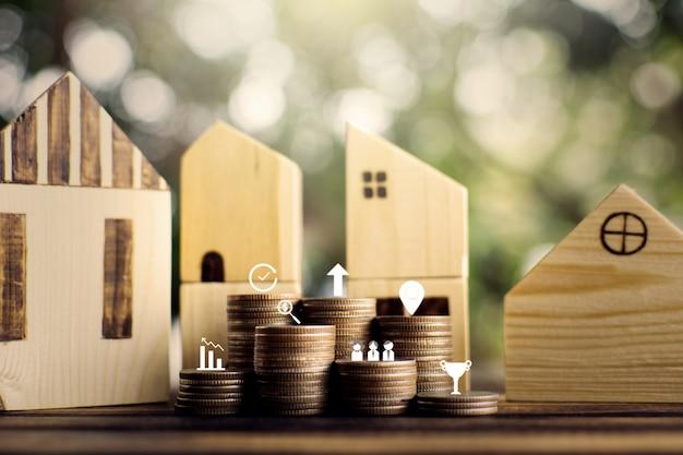 Casita de madera modelo con monedas de ahorro para residencial.