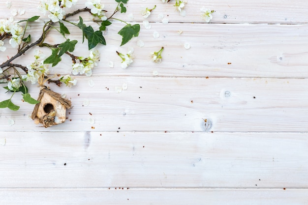 Casita para pájaros y ramas con flores en una mesa de madera con copyspace