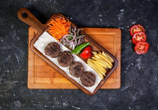 Casitas de carne con ensalada de verduras y papas fritas.