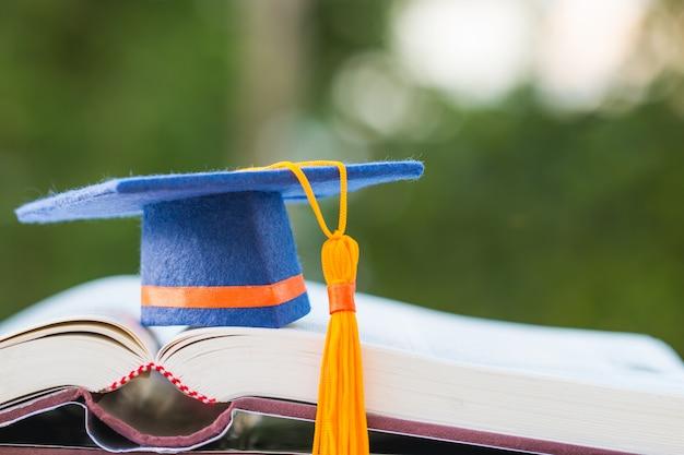 Casquillo azul de la graduación en el libro de texto de la abertura con verde claro