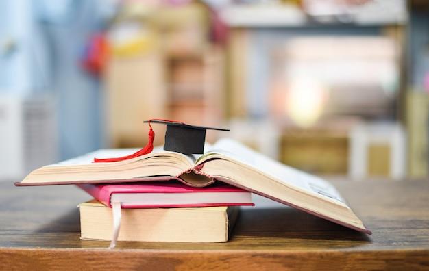 Casquillo de la graduación en un libro en la mesa de madera