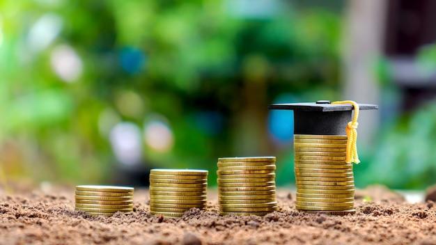 Casquillo de la graduación en una pila de monedas, naturaleza verde desenfoque concepto educación ahorrar dinero