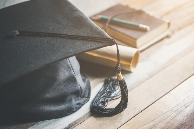 Casquillo de la graduación, sombrero con el documento del grado en el concepto de madera de la graduación de la tabla.