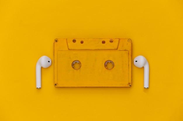 Cassette de audio retro y auriculares inalámbricos sobre fondo amarillo.