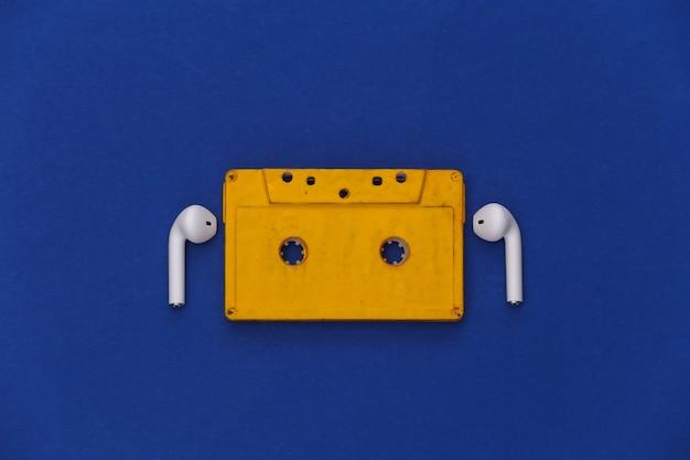 Cassette de audio retro y auriculares inalámbricos sobre fondo azul clásico.