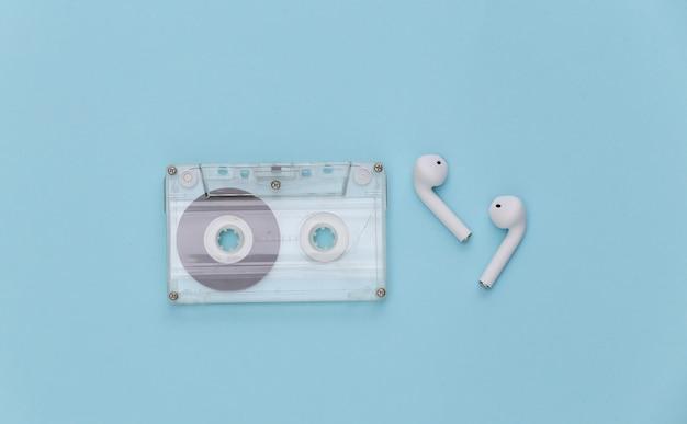Cassette de audio retro y auriculares inalámbricos sobre fondo azul.