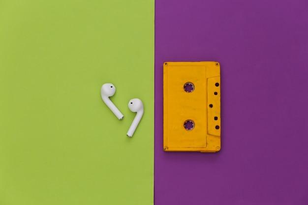 Cassette de audio retro y auriculares inalámbricos sobre un fondo verde púrpura.