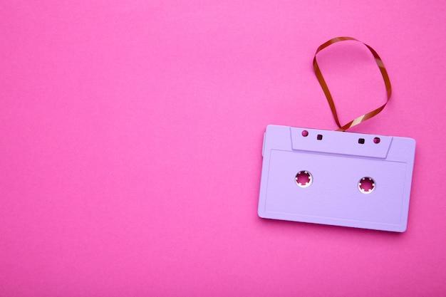 Un cassette púrpura sobre un fondo rosa. dia de la musica