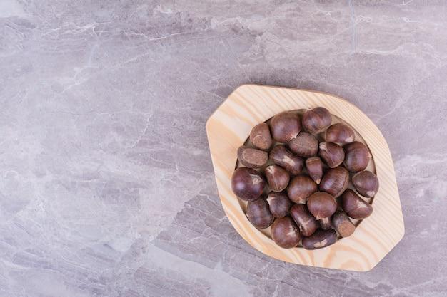 Castañas marrones en una bandeja de madera sobre la piedra