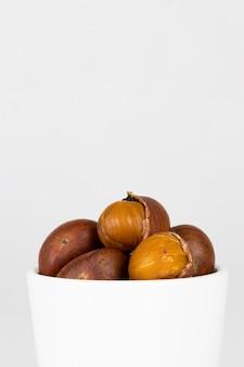 Castañas otoño comida en una taza en blanco