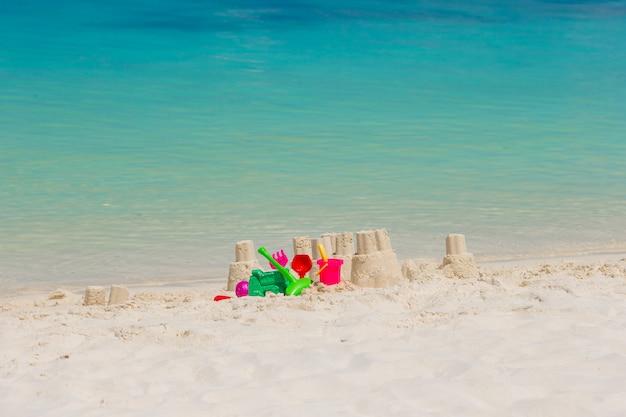 Castillo de arena en la playa blanca con juguetes de plástico para niños