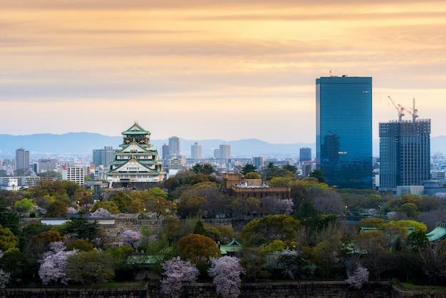 Castillo de osaka con flor de cerezo y distrito comercial del centro en japón