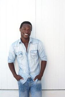 Casual hombre afroamericano sonriendo al aire libre contra el fondo blanco